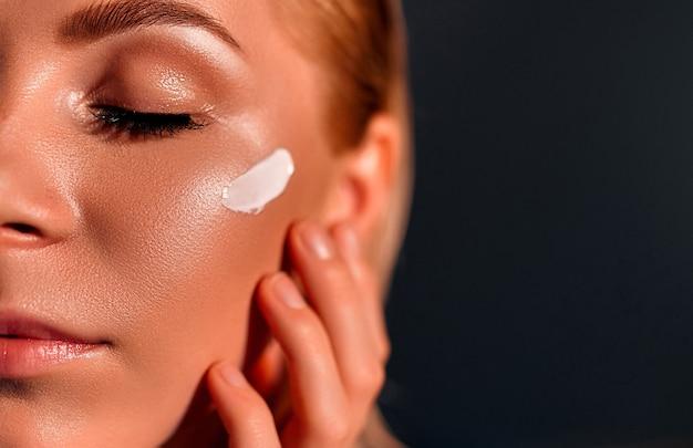 Close-up van het gezicht van een mooi meisje met een perfecte huid en reinig alle onzuiverheden dankzij hydraterende crèmes, zowel anti-aging als dag en nacht. concept van schoonheid, crèmes, huidverzorging en duidelijk.