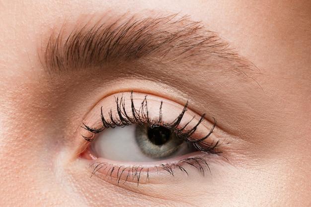 Close-up van het gezicht van een mooie blanke jonge vrouw, focus op de ogen. menselijke emoties, gezichtsuitdrukking, cosmetologie, lichaams- en huidverzorgingsconcept