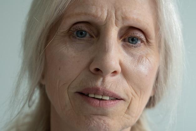 Close-up van het gezicht van een oudere vrouw met grijs haar die naar de camera kijkt