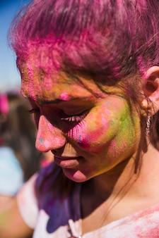 Close-up van het gezicht van een vrouw bedekt met holi kleur