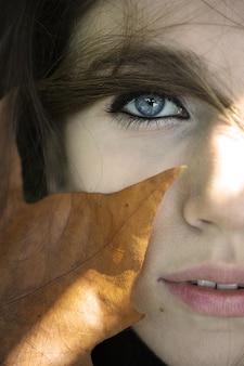 Close-up van het gezicht van een vrouw met een droog blad