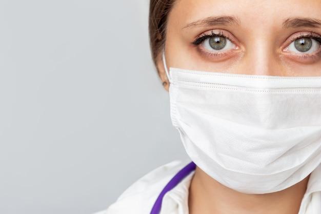 Close-up van het gezicht van een vrouwelijke arts met een medisch masker geïsoleerd op een grijze achtergrond