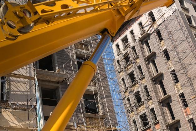 Close-up van het hefmachinemechanisme op de achtergrond van het gebouw in aanbouw