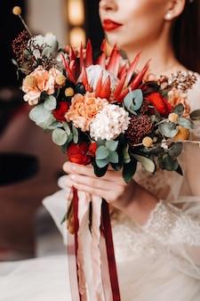 Close-up van het huwelijksboeket in de handen van de bruid.