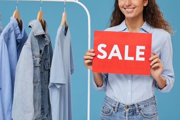 Close-up van het jonge aanplakbiljet van de vrouwenholding met verkoop die zij jeanskleren op het rek in de winkel koopt