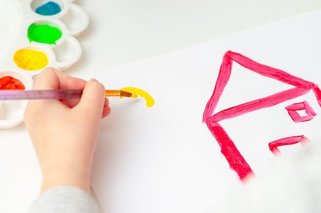 Close-up van het kind begint de zon over het huis te tekenen op wit papier.