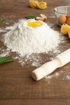 Close-up van het koken van deeg met fettuccine en eieren in de buurt met een rolbak vooraan.