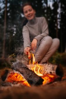 Close-up van het koken van vleesworsten in brand met mensen die op de achtergrond zitten wandelen in het bos