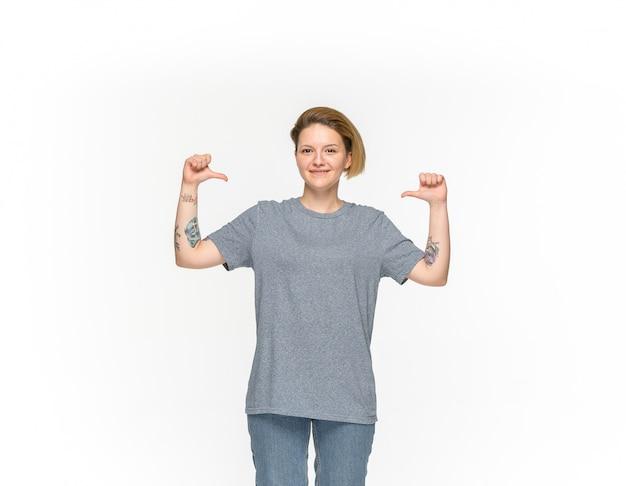 Close-up van het lichaam van de jonge vrouw in lege grijze t-shirt die op witte achtergrond wordt geïsoleerd.
