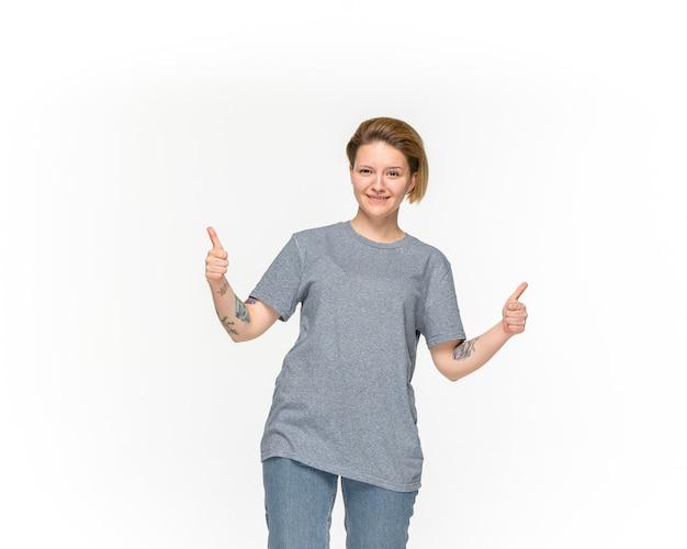 Close-up van het lichaam van de jonge vrouw in lege grijze t-shirt die op witte ruimte wordt geïsoleerd. bespotten voor ontwerpconcept