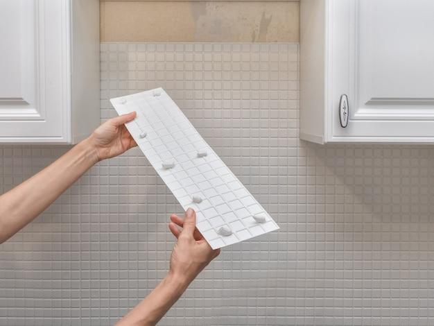 Close-up van het lijmen van een plastic wit plank paneel op de muur. man hand houden en het gebruik van lijmpistool, siliconen buis.