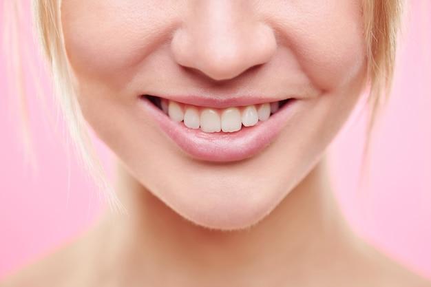 Close-up van het onderste deel van het gezicht van jonge gezonde vrouw met brede glimlach en natuurlijke make-up geïsoleerd