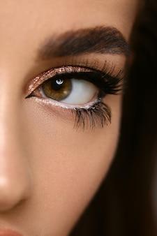 Close-up van het oog van de vrouwenkat met gouden schaduw die op zwart wordt geïsoleerd