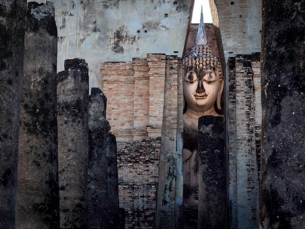 Close-up van het oude grote boeddhabeeld in de oude kerk met ruïnes van de wat sri chum-tempel, de beroemde bezienswaardigheid in het sukhothai historical park, een unesco-werelderfgoed in thailand.