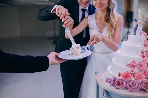 Close-up van het paar het snijden van de bruidstaart
