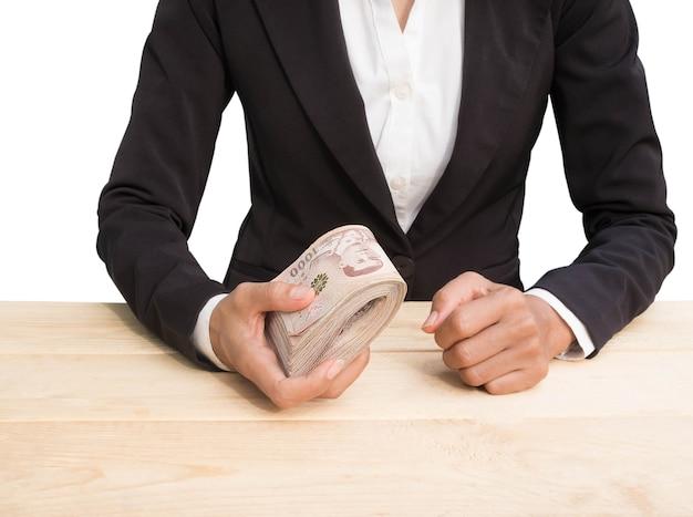 Close-up van het personeel van het vrouwen zwarte pak die het thaise bankbiljet van het geld houden