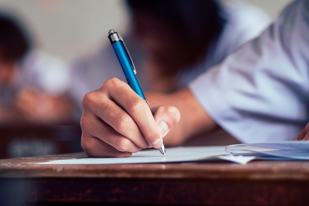 Close-up van het potlood van de studentenholding en het schrijven van definitief examen