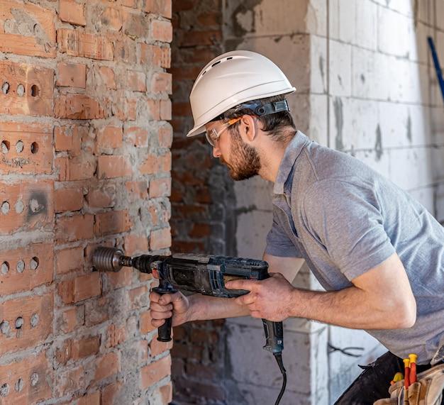 Close-up van het proces van het boren van een bakstenen muur op een bouwplaats