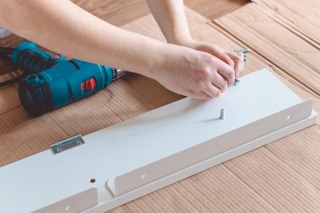 Close-up van het proces van installatie een meubilair met elektrische schroevedraaier