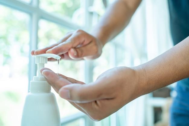 Close-up van het reinigen van handen met ontsmettingsgel, was uw handen met alcoholgel.