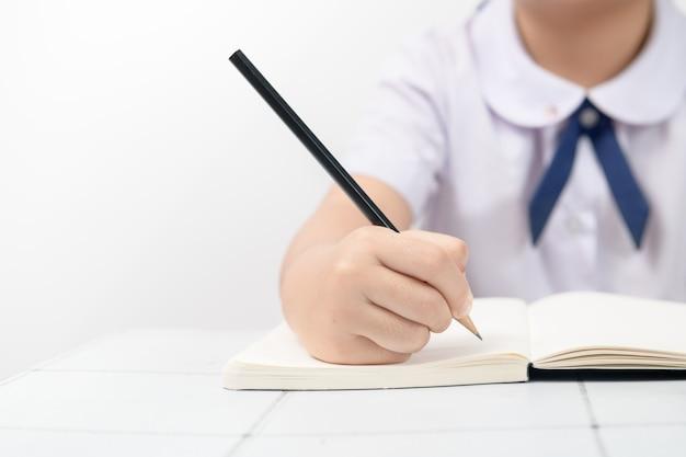 Close-up van het schrijven van handen van uniforme studenten