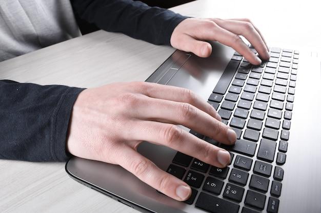 Close-up van het typen op laptop toetsenbord van mannelijke handen