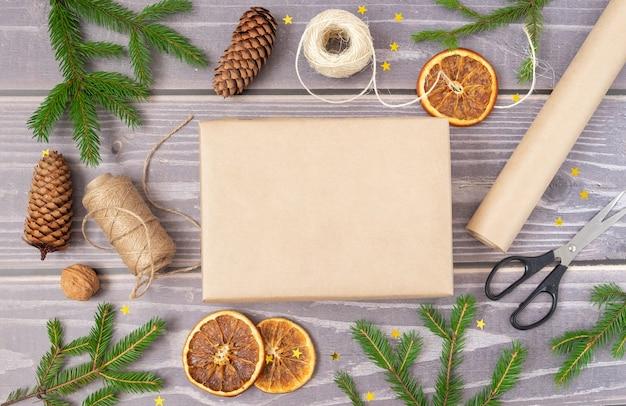 Close-up van het verpakken van een kerstcadeau. kerstdecor en recyclebaar verpakkingsmateriaal.