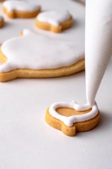Close-up van het versieren van schattige halloween peperkoekkoekjes met glazuur slagroom crème topping bag.