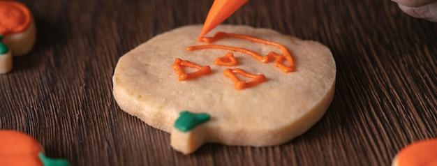 Close-up van het versieren van schattige halloween pompoen peperkoek koekjes met glazuur