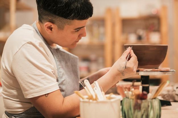 Close-up van het vrouwelijke hand schilderen op de ceramische kom met hulpmiddelen