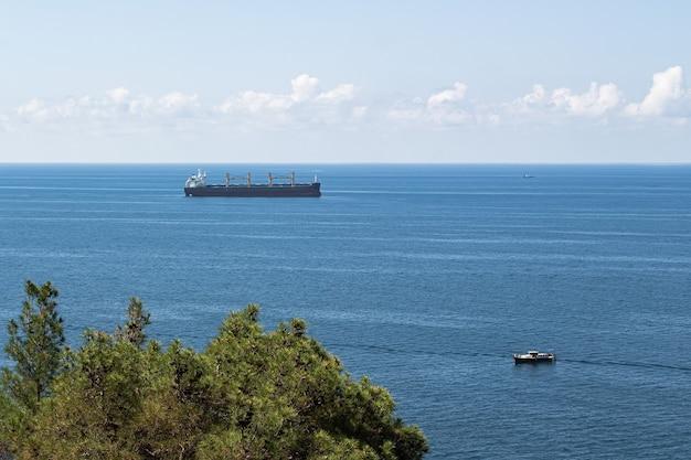 Close-up van het zeegezicht blauwe zee wolken boven de horizon en vrachtschepen op de voorgrond
