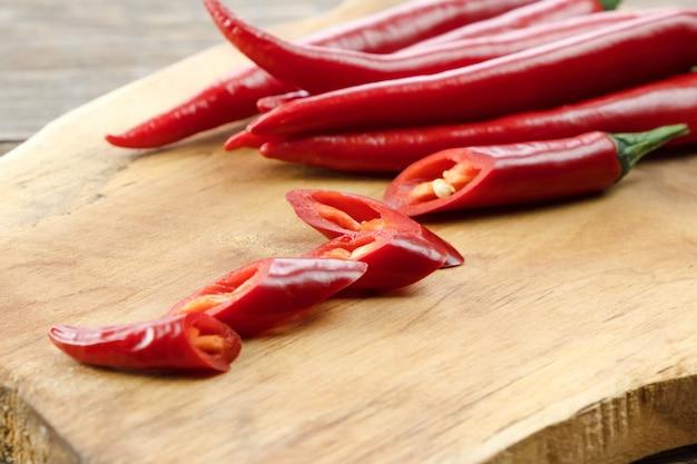 Close-up van hete chili pepers, paprika in stukjes gesneden op een houten bord