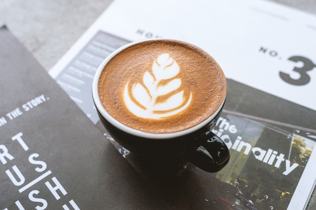 Close-up van hete koffie over tijdschriften