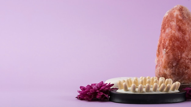 Close-up van himalayan roze steenzout; massageborstel en bloem tegen purpere achtergrond