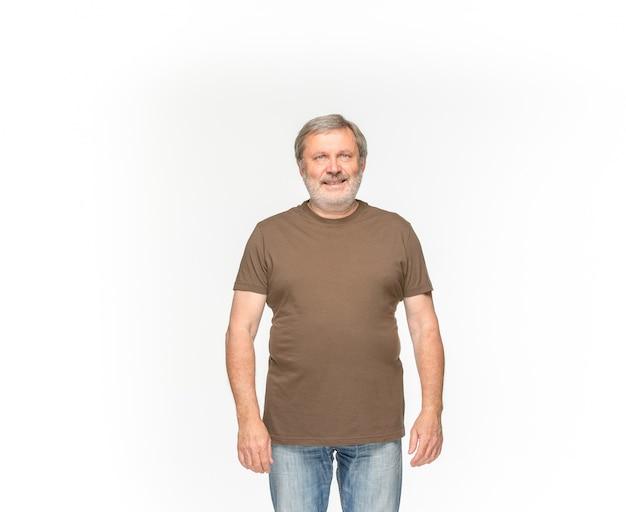 Close-up van hoger man lichaam in lege bruine t-shirt die op witte achtergrond wordt geïsoleerd. bespotten voor ontwerpconcept