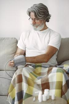 Close-up van hogere mannelijke 70-75 jaar oud die de druk meten. man om haar bloeddruk te meten. gezondheid en zorg.