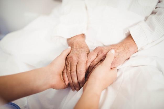 Close-up van hogere vrouw en verpleegstersholdingshanden