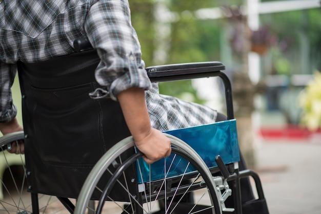 Close-up van hogere vrouwenhand op wiel van rolstoel tijdens gang in het ziekenhuis