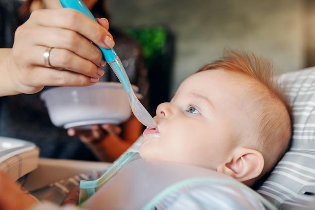 Close up van hongerige blanke babyjongen met slabbetje zittend in zijn stoel en babyvoeding eten. zijn moeder gaf hem voor het eerst eten.