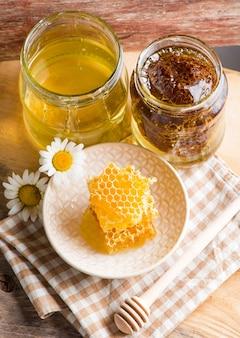 Close-up van honingraat met honing in glazen pot op houten bord, bovenaanzicht