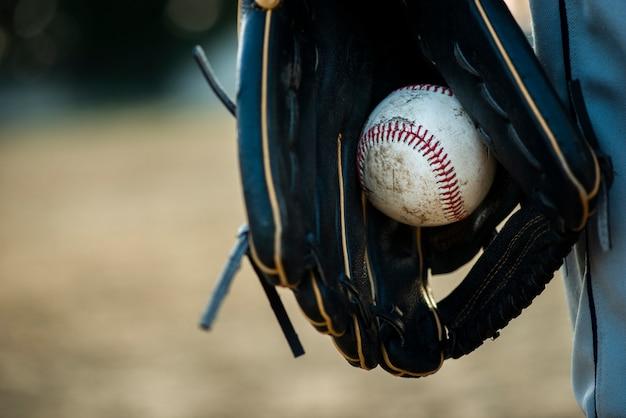 Close-up van honkbal dat in handschoen wordt gehouden