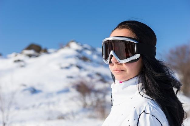 Close-up van hoofd en schouders portret van een jonge vrouw met lang donker haar dragen skibril buitenshuis terwijl het nemen van een pauze van skiën op de besneeuwde berg met felle zon, het uitzicht bewonderen