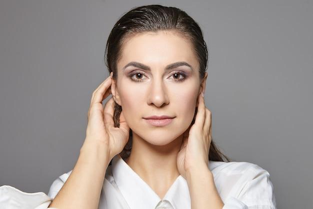 Close-up van hoofd en schouders van elegante mooie jonge blanke brunette vrouw met bruine ogen en make-up dragen witte overhemd hand in hand op haar gezicht. mode, glamour en stijl