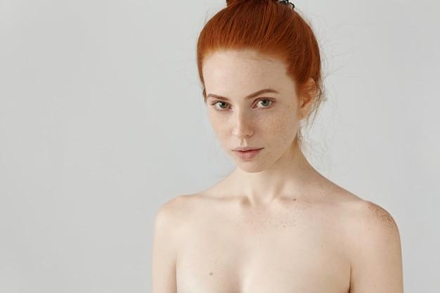 Close-up van hoofd en schouders van geweldige roodharige jonge vrouw met sproeten