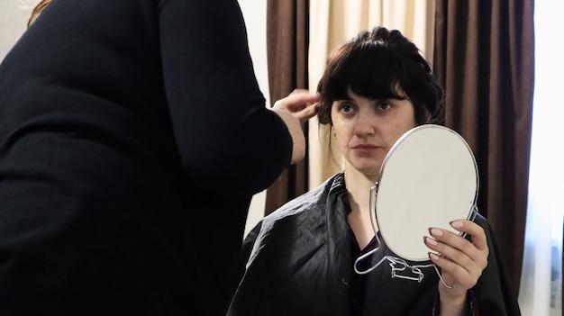 Close-up van hoofdkapper die krullend kapsel en make-up doet voor mooie vrouw met donker haar thuis. bruiloftskapsel voor de bruid.