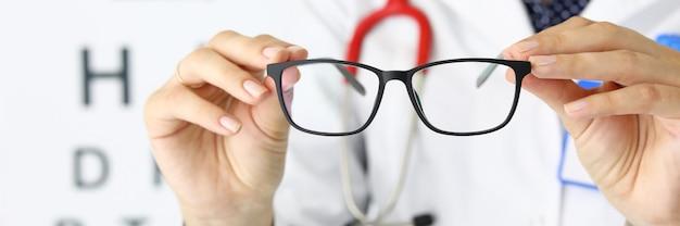 Close-up van houder van zwarte stijlvolle bril met perfect frame. bord met brief erop