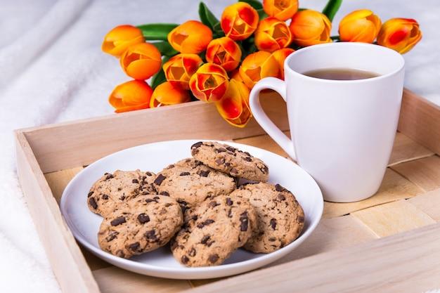 Close up van houten dienblad met chocoladeschilferkoekjes en kopje thee
