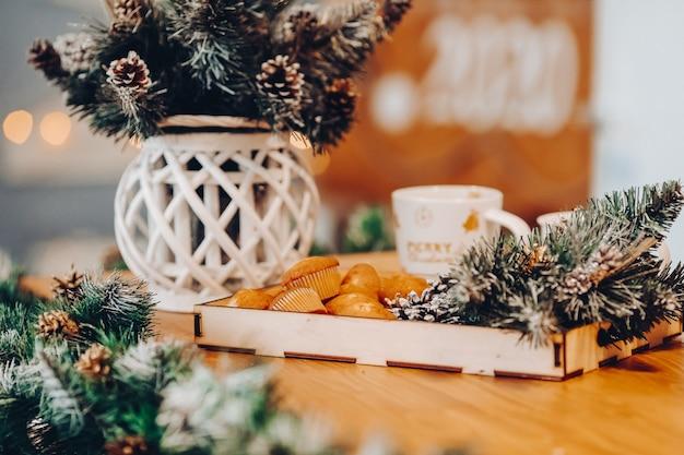 Close-up van houten dienblad met lekkere zelfgemaakte cupcakes en sparrentakken op tafel met vaas met takken met dennenappels. bokeh.