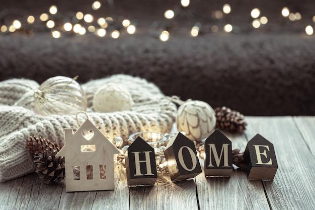 Close up van houten letters maken het woord thuis, op onscherpe achtergrond met bokeh.