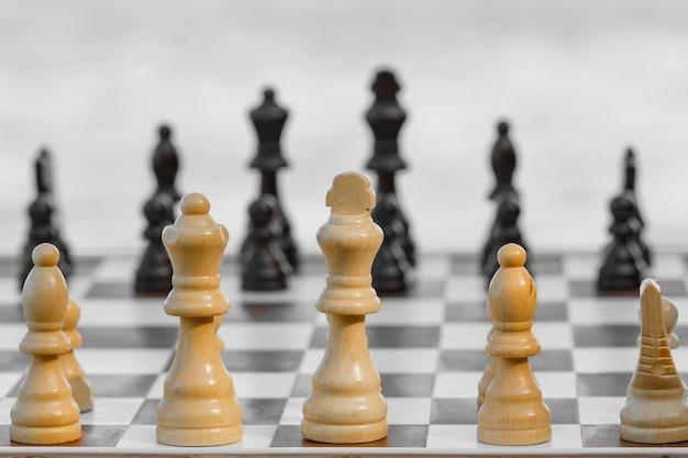 Close-up van houten schaakstukken aan boord op lichte achtergrond. selectieve focus op witte stukken. schaakspel buiten